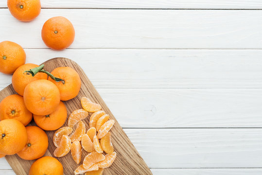 top view of peeled tangerine slices and whole ripe tangerines on wooden chopping board