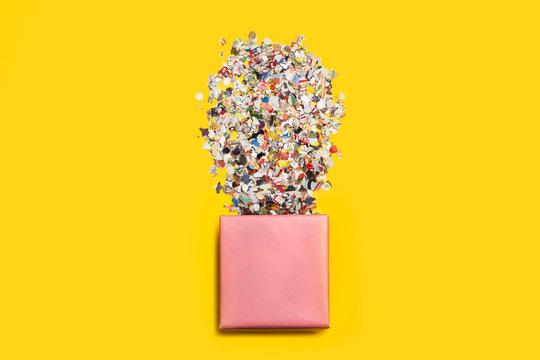 Caja abierta con confeti fiesta sobre fondo amarillo aislado. Vista superior.  Copy space