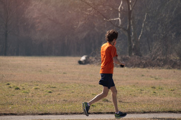 very thin boy jogging at the park - health sport activity .