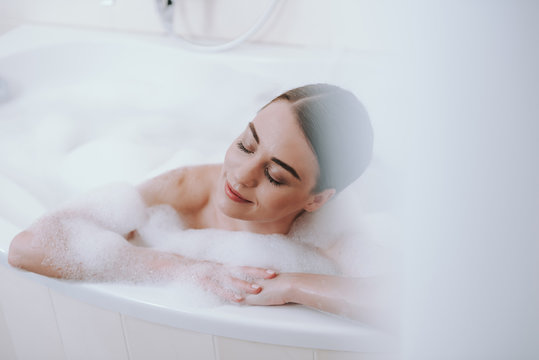 Delighted nice woman enjoying warm bath after working days