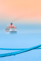 Depart for Cruise Travel / Blue rope harbor detail, departed cruise ship at blurred background (copy space)