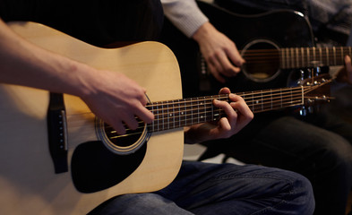 Two people duet playing a melody on acoustic six-string guitars at home in ordinary everyday clothes