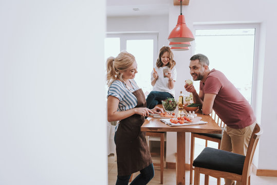 Happy family spending time together in kitchen while preparing for dinner