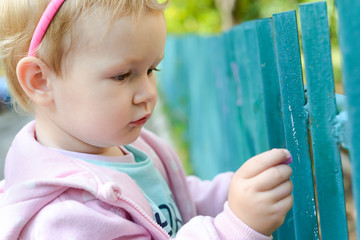 Cute baby girl stay near the fence and focused on something. The child carefully paints the chalk. Paint a green fence. Walking with the baby in the summer or in spring. The child will know the world.