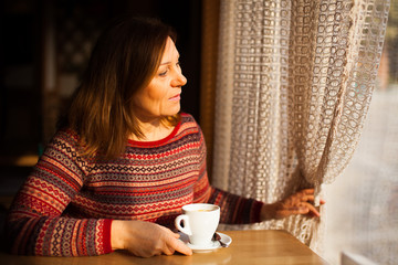 Middle aged lady in striped sweater looking throught the window with a cup of coffee
