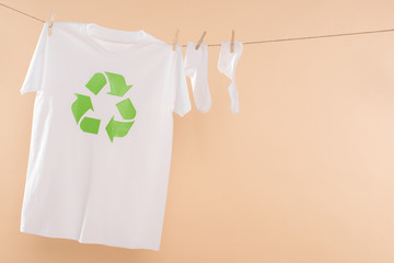 t-shirt with recycling sign on clothesline near white socks isolated on beige, environmental saving concept