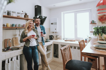 Loving couple holding glasses of wine and spending time together at home