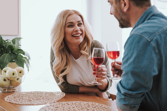 Beautiful blond woman with alcoholic drink spending time with husband at home