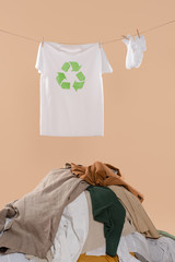 t-shirt with recycling sign on clothesline near white socks and pile of clothing on beige background, environmental saving concept