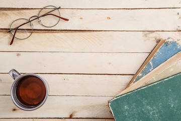 Vintage mug with drink and vintage books on wooden background. Top view