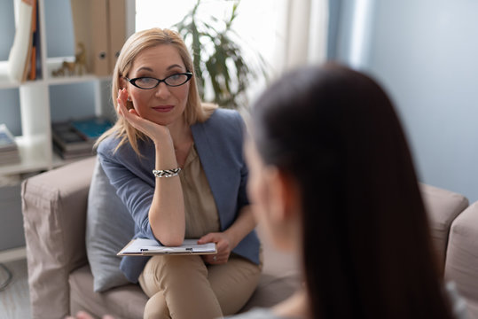 Psychologist with clipboard looking attentively at patient