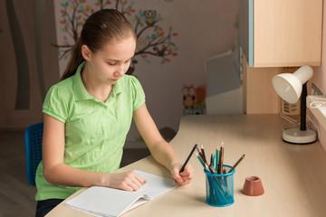 Cute little girl left-handed writing her homework