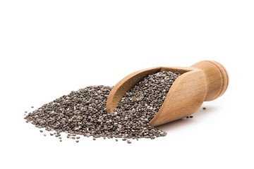 Pile or heap of chia seeds and a small wooden scoop seen from the front and isolated on white background