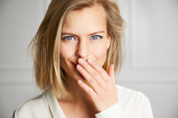 Beautiful girl with hand over mouth, portrait