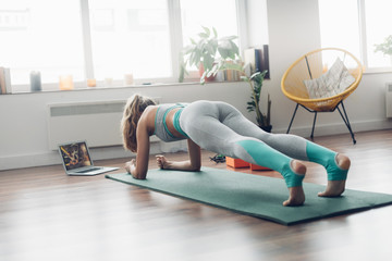 Young lady doing plank aerobics practice at home