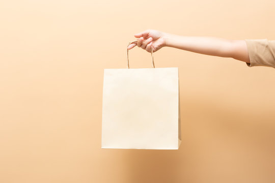 Hand holding a paper bag isolated on background