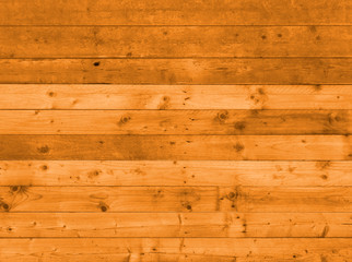 warm brown wooden plank wall or floor with grainy knotted boards made of old reused timber