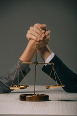 selective focus of business colleagues arm wretsling on wooden table with scales of justice on grey