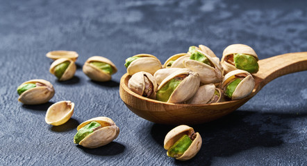Pistachios  in wooden spoon  on black table,close-up