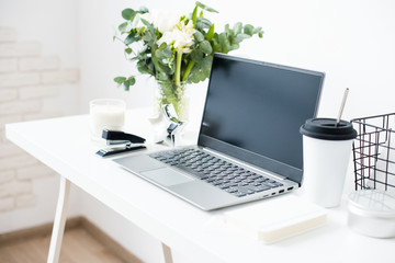 Hipster bloggers work place, laptop and flowers on white tabletop