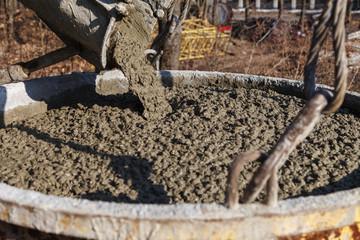 Construction workers pouring wet concrete using concrete bucket