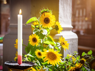sunflowers with a burning candle in a church