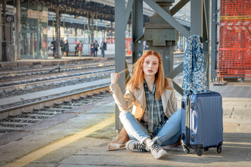 A girl with suitcase at the train station for vacations