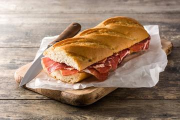 Spanish serrano ham sandwich on wooden table