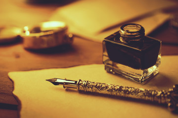 vintage literature - retro feather pen and inkwell on old parchment paper