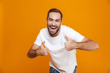 Image of handsome guy 30s in t-shirt rejoicing and showing thumbs up while standing, isolated over yellow background