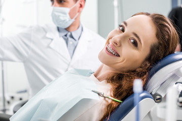 selective focus of beautiful woman in braces during examination of teeth near dentist