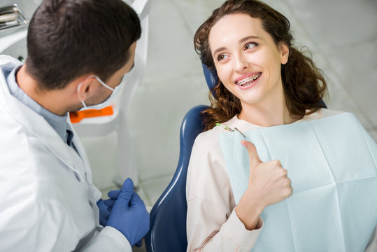 selective focus of woman in braces smiling while showing thumb up near dentist during examination