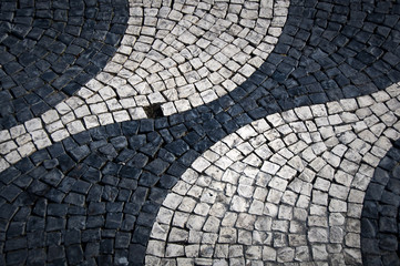 Shapes and patterns of a cobbled street of Lisbon (Portugal). Rounded and waving black and white shapes with an empty cobblestone space