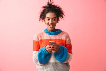 Happy beautiful young african woman posing isolated over pink wall background using mobile phone. Wall mural