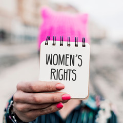 woman with a pink hat and the text womens rights