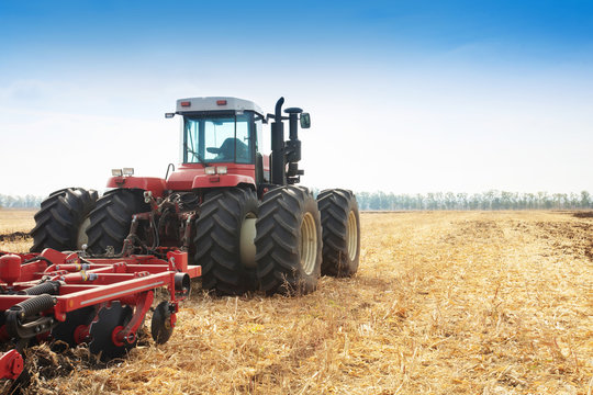 Modern tractor in the field during planting. The concept of agricultural industry.