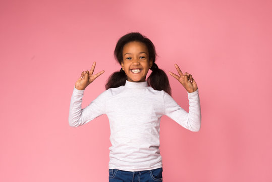 Happy preteen girl showing peace sign, pink background