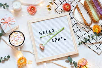 Hello April concept spring flat lay on the white blanket. Breakfast in the bed top view card with text