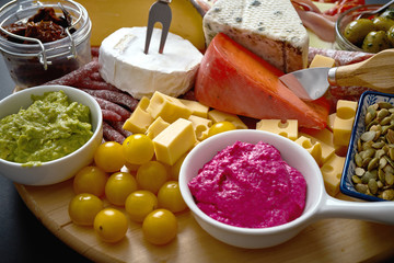Antipasti board with different cheese and meat snacks with hummus and olives on wooden board