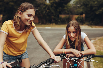 Two girls on bicycles on street
