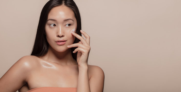 Woman applying beauty product on face