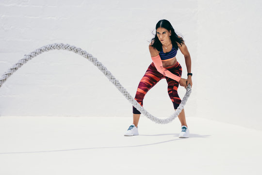 Woman doing fitness workout using battle rope
