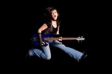 Young Rocker Woman Jumping with Bass Guitar - Rock Musician Guitarist