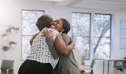 Fototapeta Two female black african freelancers embraced in a friendly hug in a modern co-working space obraz