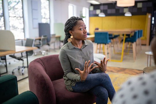 Job interview in co-working space by recruiter. Black african woman in her twenties being interviewed for a job position