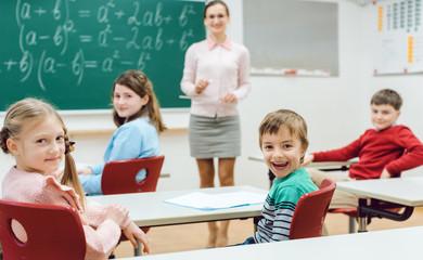 Schüler in der Klasse melden sich, um eine Frage zu beantworten