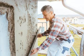 Verputzer streicht Putz an einer Außenwand glatt