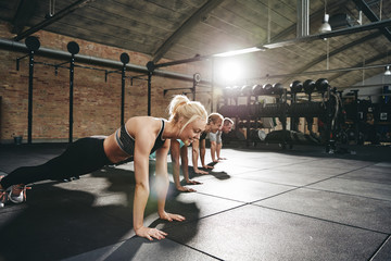 Fit young people doing pushups during a gym workout class
