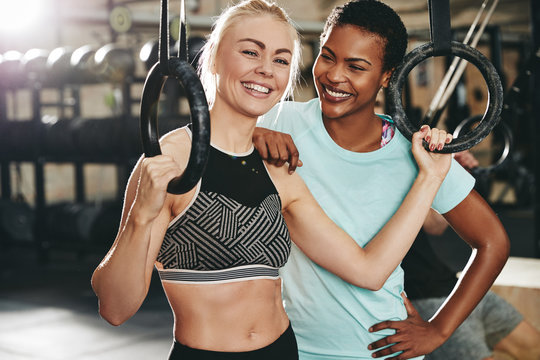 Smiling female friends working out with rings at the gym