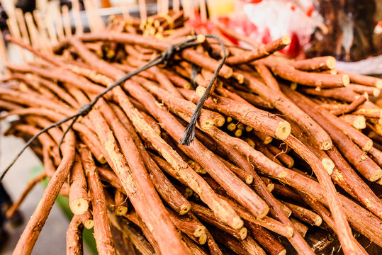 Stacks of dried licorice branches for sale.